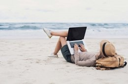 Young woman using laptop computer on a beach. Freelance work con